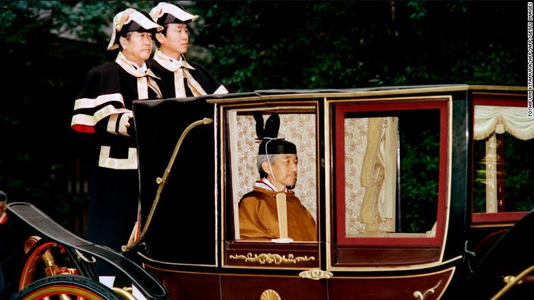 Japanese Emperor Akihito sits in a carriage on his way to perform a ritual to mark the completion of his enthronement on November 28, 1990.