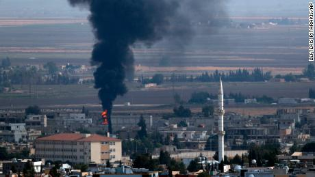 In this photo taken from the Turkish side of the border between Turkey and Syria, in Ceylanpinar, Sanliurfa province, southeastern Turkey, smoke billows from a fire in Ras al-Ayn, Syria, Friday, Oct. 18, 2019. Fighting broke out in the morning hours in the Syrian border town which has been a flashpoint in the fight between Turkey and Kurdish forces despite a U.S.-brokered cease-fire that went into effect overnight. The fighting died down in mid-morning. (AP Photo/Lefteris Pitarakis)