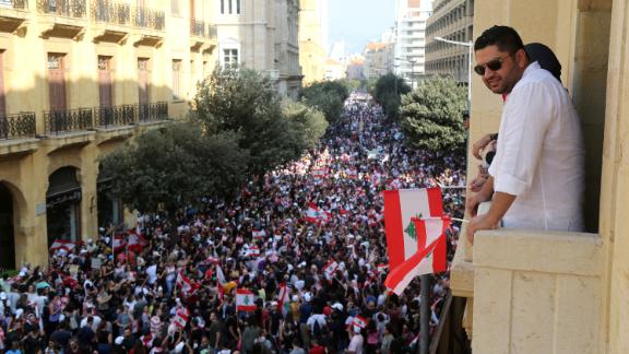A man holds a Lebanese flag as he stands on a balcony during a protest.