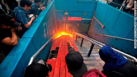 Protesters burn an entrance to Santa Lucia metro station in Santiago on Friday.