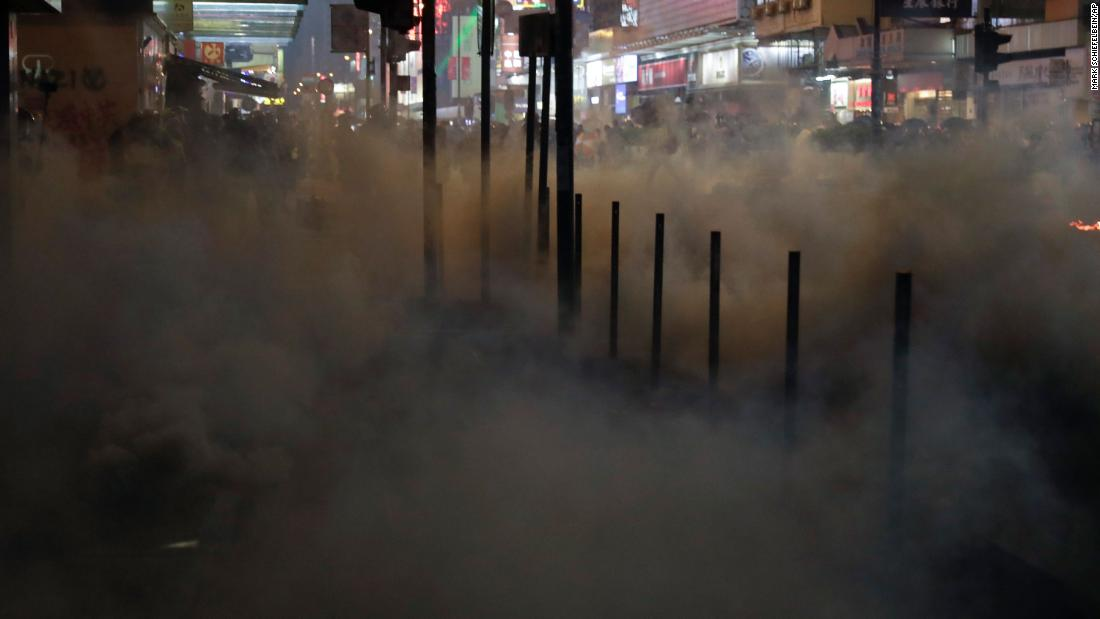 Protesters scatter as tear gas fills a street in Hong Kong on October 20.