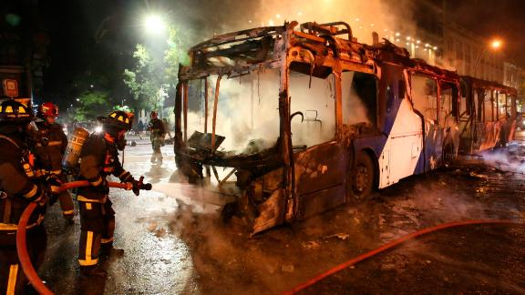 Firefighters put out the flames on a burning bus during a protest in Santiago, Friday, October 18, 2019.