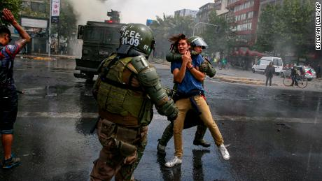 A demonstrator is detained by the police during a protest in Santiago, Chile, Saturday, October 19, 2019.