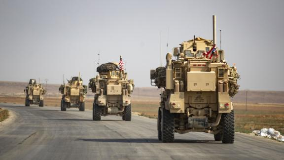 US military vehicles drive after pulling out of their base in the northern Syrian town of Tal Tamr on Sunday, October 20.