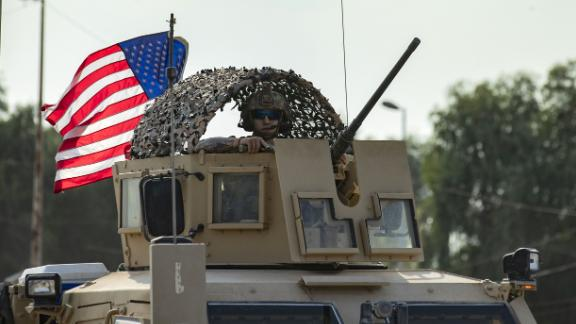 A US service member looks out of an armored vehicle as troops pull out of their base in Tal Tamr.