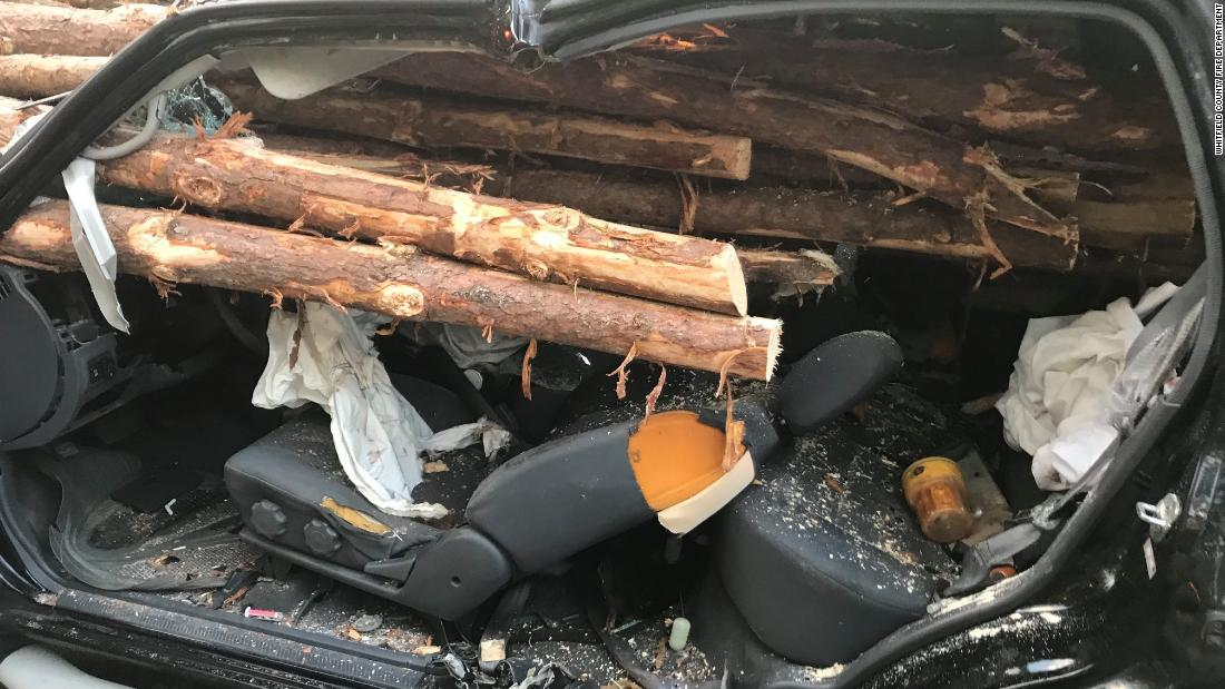 A driver is rescued alive after his car is impaled by logs from a truck