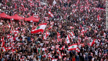 Lebanese demonstrators wave national flags as they take part in a rally in the capital Beirut's downtown district on October 20, 2019. - Thousands continued to rally despite calls for calm from politicians and dozens of arrests. The demonstrators are demanding a sweeping overhaul of Lebanon's political system, citing grievances ranging from austerity measures to poor infrastructure. (Photo by Patrick BAZ / AFP) (Photo by PATRICK BAZ/AFP via Getty Images)