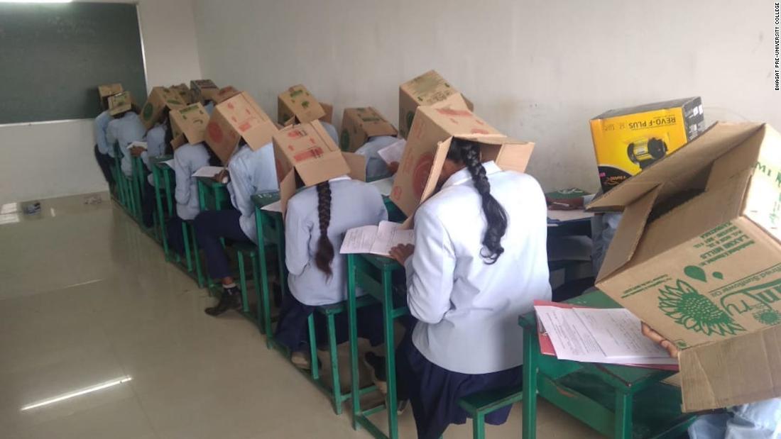 Die Schüler tragen Kartons auf Ihren Köpfen während der Prüfung