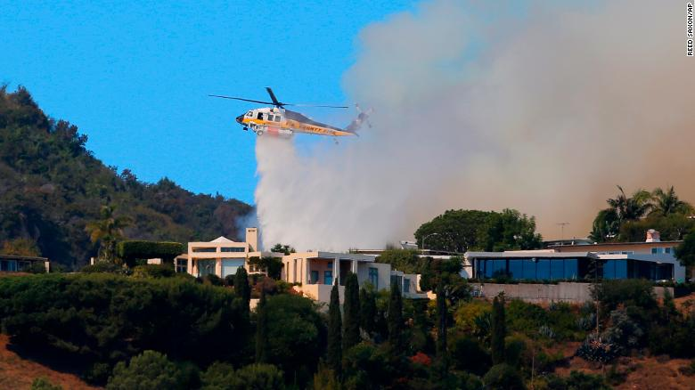 A helicopter makes a water drop as flames threaten homes on a ridgeline in the Pacific Palisades area of Los Angeles.