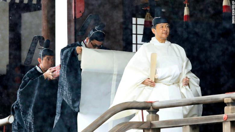 """Japan's Emperor Naruhito, in a white robe, leaves after praying at """"Kashikodokoro"""", one of three shrines at the Imperial Palace, in Tokyo, on October 22, 2019."""