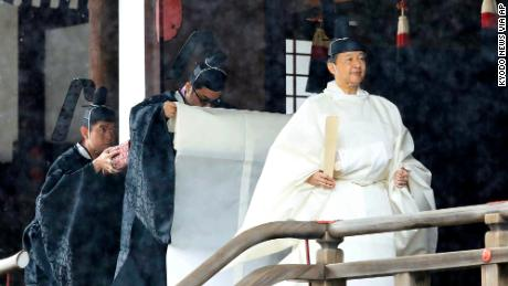 Japan's Emperor Naruhito in a white robe leaves after praying in