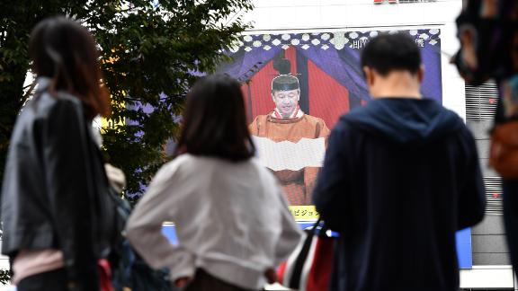 People watch Japan's Emperor Naruhito proclaim his enthronement during a live broadcast in Tokyo.