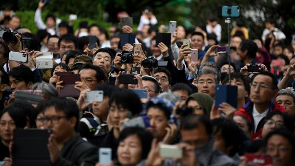 A crowd gathers to watch firing artilleries marking Japan's Emperor Naruhito's enthronement.