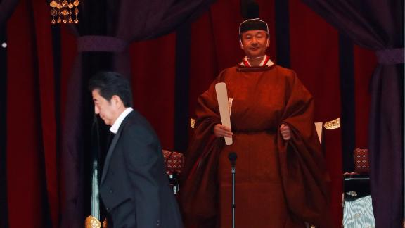 Japan's Prime Minister Shinzo Abe walks past Emperor Naruhito during his enthronement ceremony.