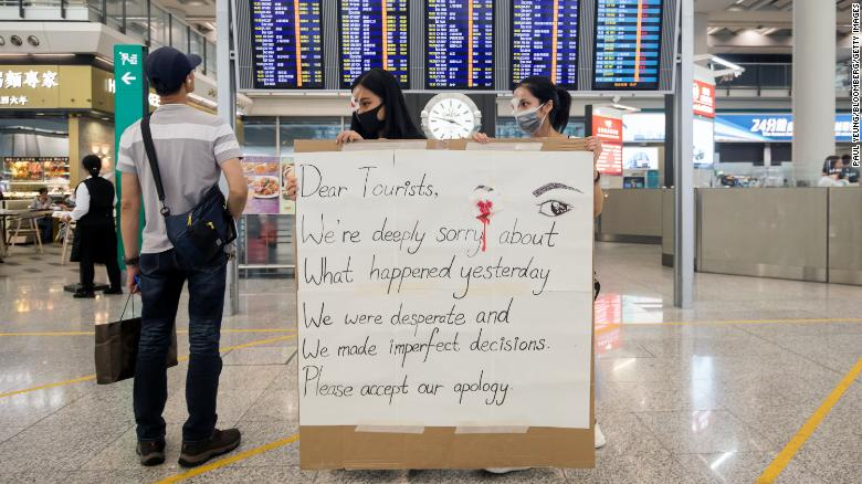 Demonstrators hold an apology sign at the Hong Kong International Airport on August 14, 2019.