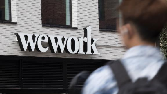 A pedestrian walks past a logo for WeWork the co-working office space, operated by the parent company We Co., on City Road in London, U.K., on Monday, Oct. 7, 2019. While WeWork has been rapidly expanding in Canada, the New York-based company is facing challenges on multiple fronts with Landlords in London and New York amongst the most exposed to any further deterioration at the co-working firm. Photographer: Bryn Colton/Bloomberg via Getty Images