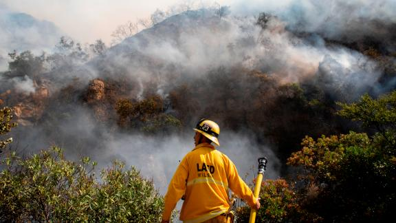 A firefighter looks out over the flames of the Palisades Fire on Oct. 21, 2019, in the Pacific Palisades section of Los Angeles.