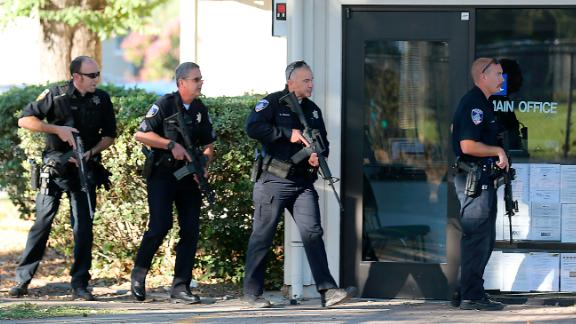 Police officers search for a suspect in the shooting near Ridgway High School in Santa Rosa, California.