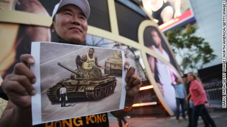 A pro-Hong Kong activist holds an image depicting LeBron James aboard a Chinese tank in Tiananmen Square before the Los Angeles Lakers season opening game against the against the LA Clippers outside Staples Center on October 22, 2019.
