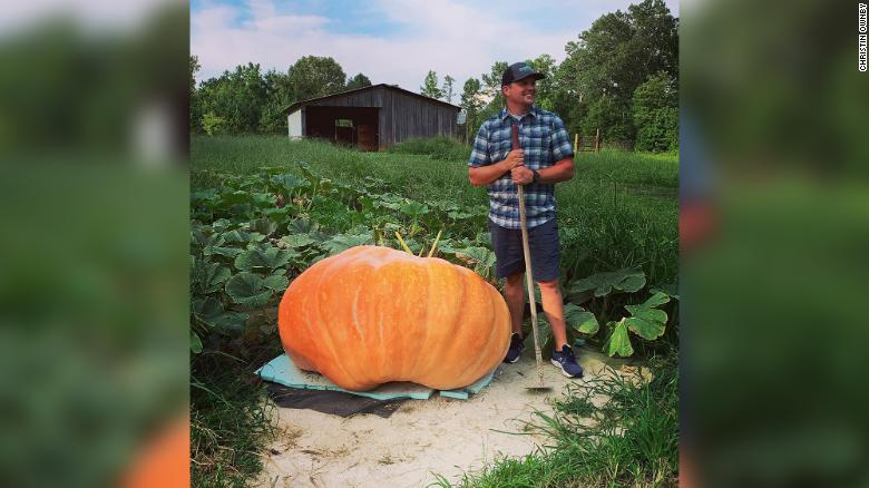 Justin Ownby standing next to his giant pumpkin.