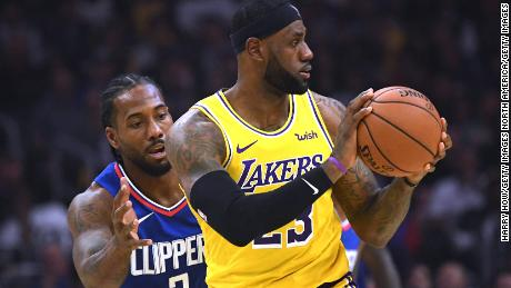 LeBron James, right, of the Lakers is defended by Kawhi Leonard of the Clippers during the opening game for both Los Angeles teams on Tuesday.