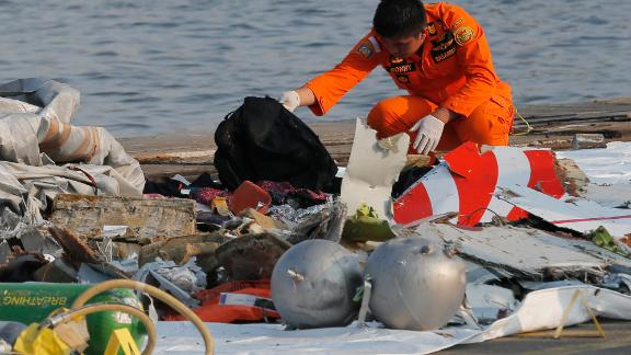 A member of Indonesian Search and Rescue Agency (BASARNAS) inspects debris believed to be from Lion Air passenger jet that crashed off Java Island at Tanjung Priok Port in Jakarta, Indonesia Monday, Oct. 29, 2018. A Lion Air flight crashed into the sea just minutes after taking off from Indonesia's capital on Monday in a blow to the country's aviation safety record after the lifting of bans on its airlines by the European Union and U.S. (AP Photo/Tatan Syuflana)