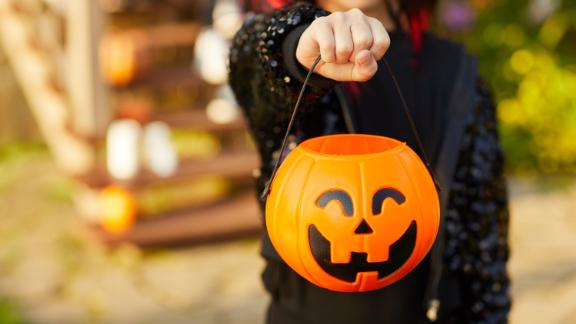 Closeup of unrecognizable little girl wearing Halloween costume and holding pumpkin basket in trick or treat season, copy space; Shutterstock ID 1499358104; Job: Design