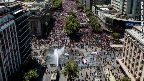 Aerial view of riot police spray on demonstrators in Santiago on October 23, 2019.