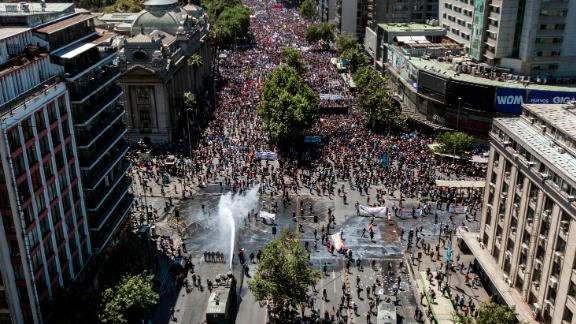 Aerial view showing riot police spraying water at demonstrators in Santiago on October 23, 2019.