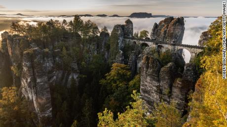 Mist hangs on the Bastei rock formation with the Basteibruecke bridge in the Elbe sandstone mountains after sunrise near Lohmen, eastern Germany, on October 7, 2019. (Photo by Robert Michael / dpa / AFP) / Germany OUT (Photo by ROBERT MICHAEL/dpa/AFP via Getty Images)