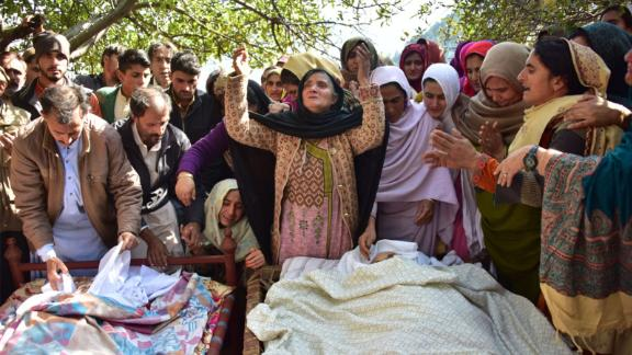 Relatives mourn next to bodies of victims of cross border shelling in Nousehri, a village in Neelum Valley, Pakistani-administered Kashmir, on October 20, 2019.