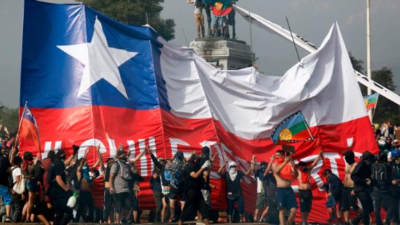 SANTIAGO, CHILE - OCTOBER 23: Demonstrators spread a giant flag of Chile as they gather at Plaza italia against President Sebastian Piñera during the sixth day of protest against President Sebastian Piñera on October 23, 2019 in Santiago, Chile. Although President Sebastian Piñera announced yesterday a few measures to improve equality, unions called for a national strike and demonstrations continue as casualties are now 18. Demands behind the protest include issues like health care, pension system, privatization of water, public transport, education, social mobility and corruption. (Photo by Marcelo Hernandez/Getty Images)