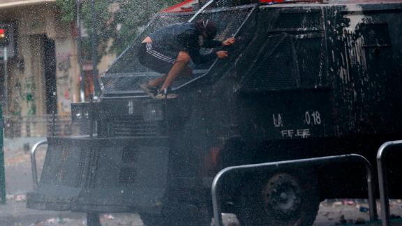A demonstrator jumps in front of a police vehicle during the sixth day of protest against President Sebastian Pinera.