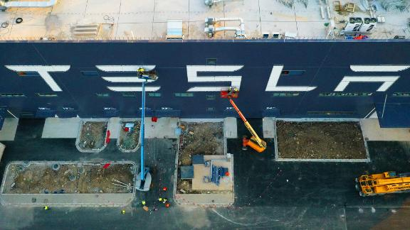 Workers on cranes installing a logo at the Tesla Gigafactory 3 earlier this month in Shanghai.