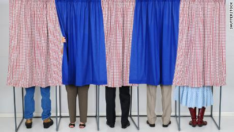 A row of five voting booths with men and women casting their ballots at a polling place. Horizontal format, only showing the legs of the voters, people are unrecognizable..; Shutterstock ID 114656170; Job: -