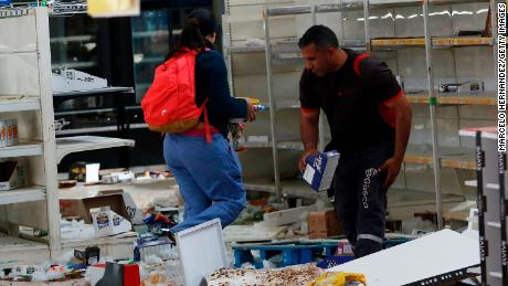 People take objects looted from a supermarket in Santiago.
