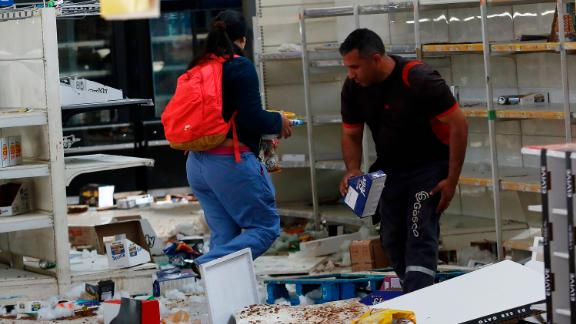 People take items from a looted supermarket in Santiago.
