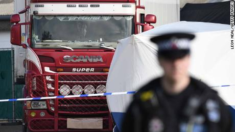 Police stand guard at the site where 39 bodies were discovered in the back of a lorry.