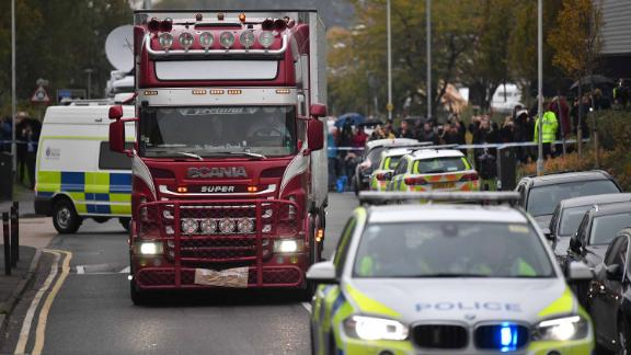 Police officers drive away a lorry (C) in which 39 dead bodies were discovered sparking a murder investigation at Waterglade Industrial Park in Grays, east of London, on October 23, 2019. - British police said 39 bodies were found near London Wednesday in the container of a truck thought to have come from Bulgaria. Essex Police said the people were all pronounced dead at the scene in an industrial park in Grays, east of London. Early indications suggest the victims are 38 adults and one teenager. A 25-year-old man from Northern Ireland has been arrested on suspicion of murder. (Photo by Ben STANSALL / AFP) (Photo by BEN STANSALL/AFP via Getty Images)