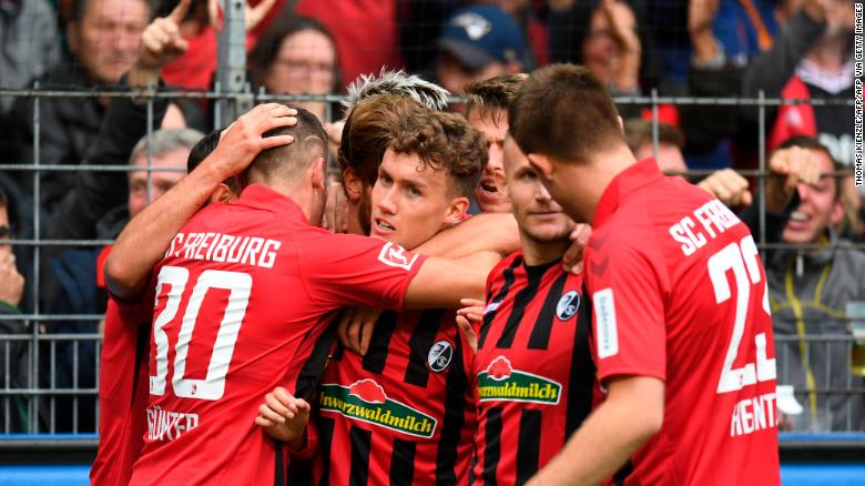 Freiburg's German forward Luca Waldschmidt (C) celebrates with teammates after scoring against Borussia Dortmund.