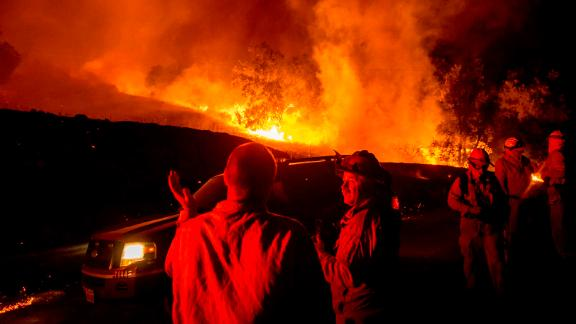 Firefighters confer while battling the Kincade Fire near Geyserville, California, on Thursday.