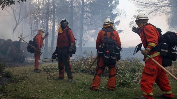 Firefighters from Holton Fire Camp 16 work to contain the Tick Fire behind a home in the Santa Clarita area of Los Angeles on Thursday, October 24, 2019.