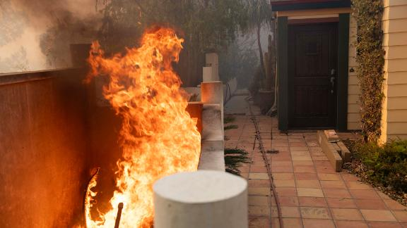 Flames burn near the entrance of a home during the Tick Fire in the Santa Clarita area of Los Angeles on Thursday.