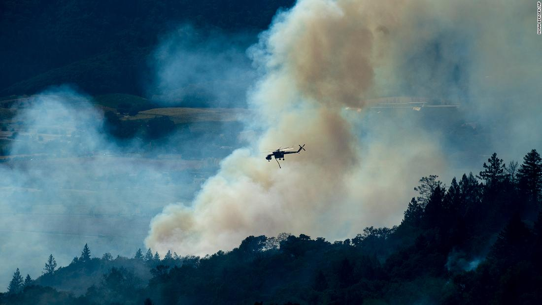 A helicopter passes a smoke plume on October 24.
