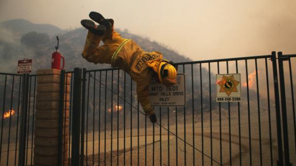 A Cal Fire firefighter hops over a locked gate while working the Tick Fire on Thursday in Canyon Country, California.