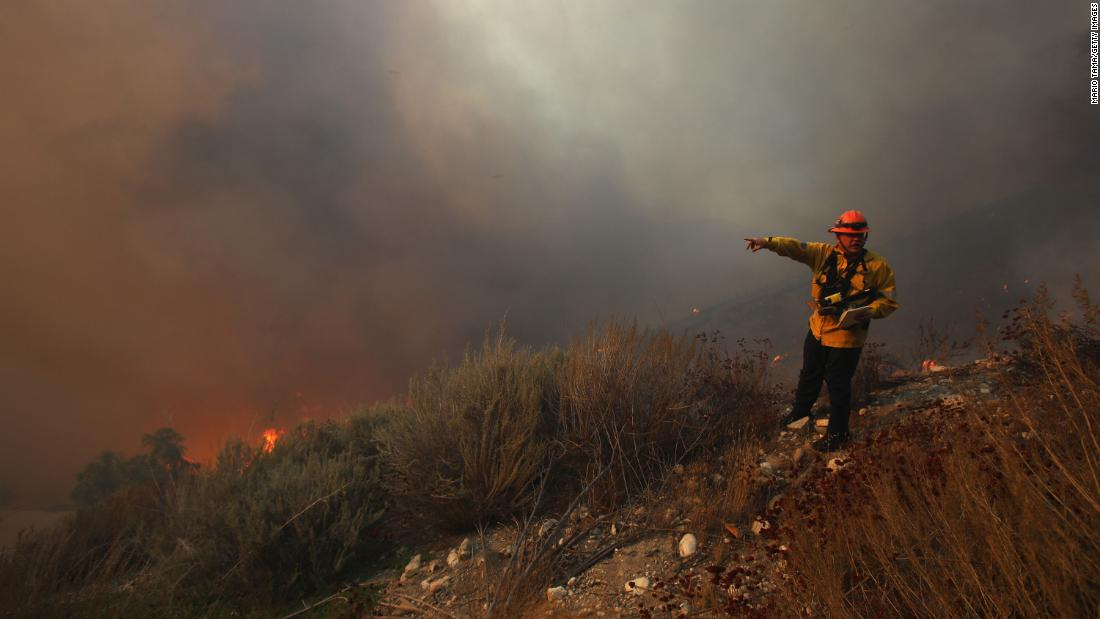 A Los Angeles County firefighter monitors the area as the Tick Fire burns near homes in Canyon Country on October 24.