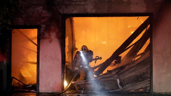 A firefighter works the scene of a burned-out home in Santa Clarita on October 24.