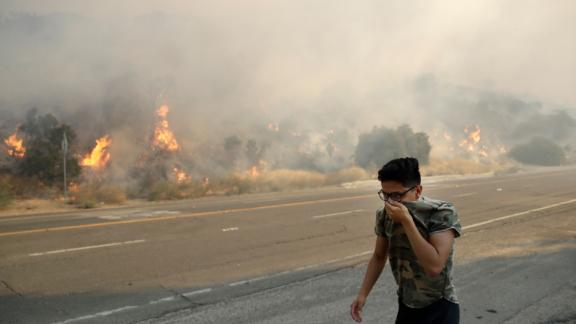Brandon Mani covers his face from the smoke as he walks along Highway 14 in Santa Clarita.