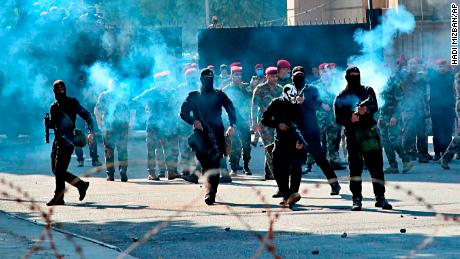 Security forces fire tear gas to disperse anti-government protesters in Baghdad.