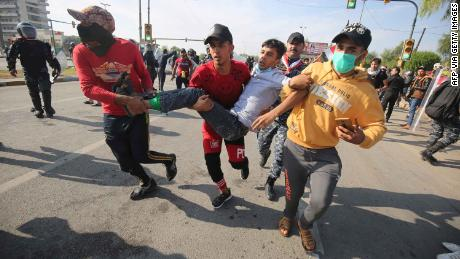 Iraqis carry a wounded demonstrator after security forces fired tear gas to disperse anti-government protests in Baghdad on October 25.